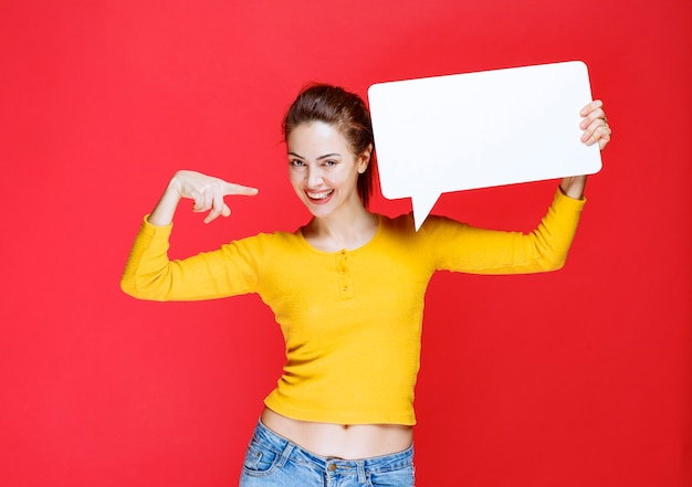 Dziewczyna w żółtej koszuli trzymająca prostokątną tablicę informacyjną