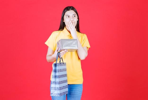 Dziewczyna w żółtej koszuli trzymająca torbę na zakupy i srebrne pudełko upominkowe i wygląda na przerażoną i przerażoną