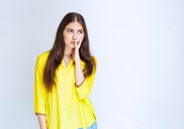 Dziewczyna w żółtej koszuli wygląda na przerażoną i zachwyconą.