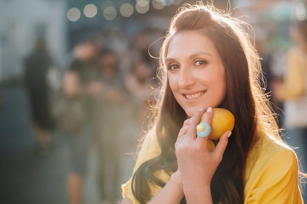 Dziewczyna w żółtej koszuli z cytrynami w rękach na miejskiej ulicy. portret kobiety w kolorze żółtym.