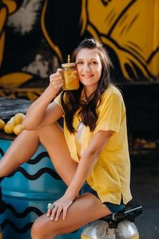 Dziewczyna w żółtej koszuli z sokiem z cytryny w dłoniach w miejskiej kawiarni na ulicy. portret kobiety w kolorze żółtym.