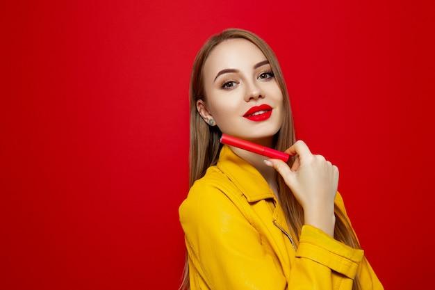 Dziewczyna w żółtej kurtce na czerwonym tle