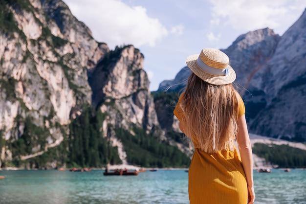 Dziewczyna w żółtej sukience i słomkowym kapeluszu nad jeziorem lago di braies w dolomitach. niesamowita podróż.