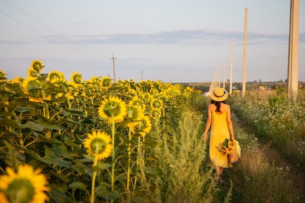 Dziewczyna w żółtej sukience i słomkowym kapeluszu spaceruje po środku dużego pola słoneczników trzymając bukiet słoneczników w słomianej torbie. piękny słoneczny wieczór.