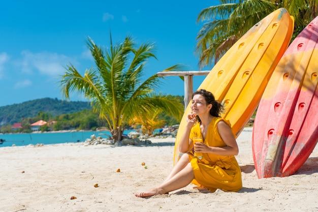 Dziewczyna w żółtej sukience na tropikalnej piaszczystej plaży pracuje na laptopie w pobliżu kajaków i pije świeże mango. praca zdalna, udany niezależny. działa na wakacjach.
