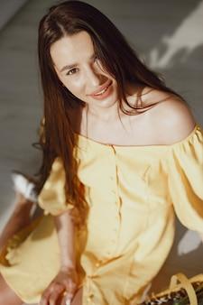 Dziewczyna w żółtej sukience z koszem w rękach obchodzi wielkanoc