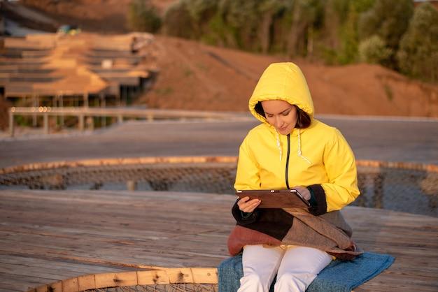 Dziewczyna w żółtej wiatrówce siedzi wczesnym rankiem na drewnianym molo