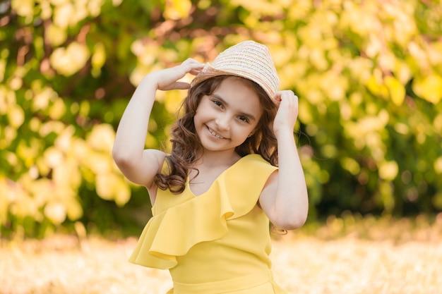 Dziewczyna w żółtych ubraniach siedzi na trawie w parku latem. zdjęcie wysokiej jakości