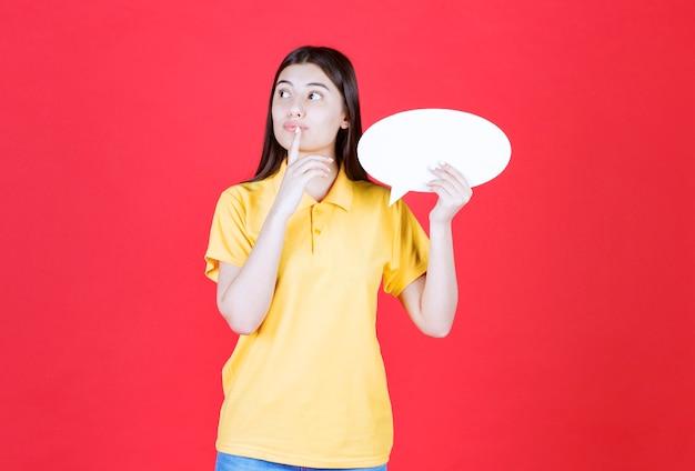 Dziewczyna w żółtym dresscode trzyma owalną tablicę informacyjną i wygląda na zamyśloną i niezdecydowaną