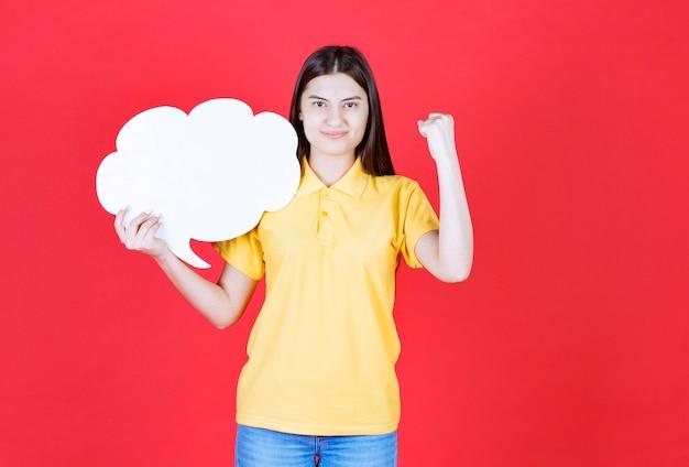 Dziewczyna w żółtym dresscode trzyma tablicę informacyjną w kształcie chmury i pokazuje swoją pięść