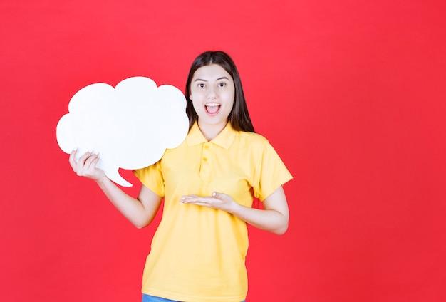 Dziewczyna w żółtym dresscode trzyma tablicę informacyjną w kształcie chmury i wygląda na podekscytowaną lub przerażoną