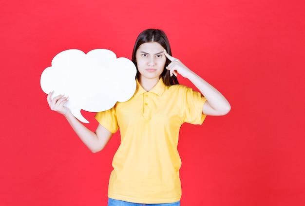Dziewczyna w żółtym dresscode trzyma tablicę informacyjną w kształcie chmury i wygląda na zdezorientowaną lub zamyśloną