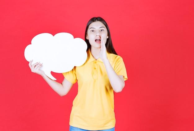 Dziewczyna w żółtym dresscode trzyma tablicę informacyjną w kształcie chmury i zaprasza kogoś obok siebie.