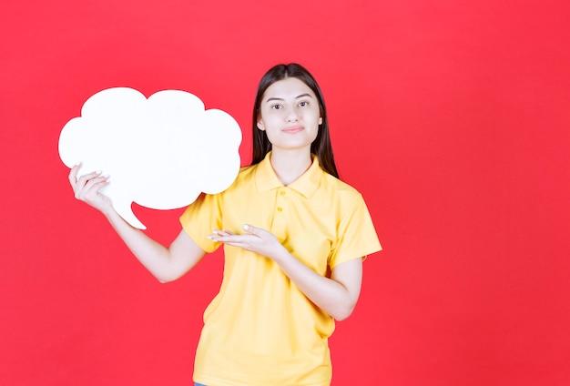 Dziewczyna w żółtym dresscode trzymająca tablicę informacyjną w kształcie chmury
