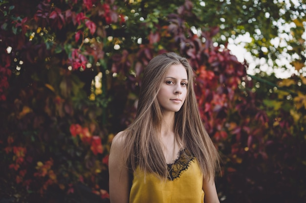 Dziewczyna w żółtym jedwabniczym wierzchołku w atumn parku.