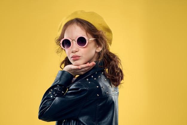 Dziewczyna w żółtym kapeluszu ciemne okulary modne ubrania studio styl życia dzieciństwo