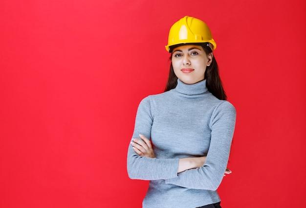 Dziewczyna w żółtym kasku skrzyżowanie ramion i wyglądający jak profesjonalista.