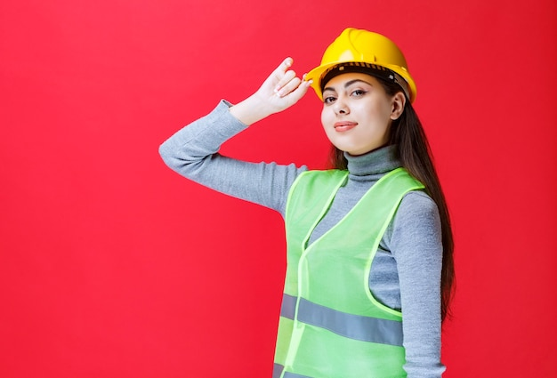 Dziewczyna w żółtym kasku trzymając hełm i pozowanie.