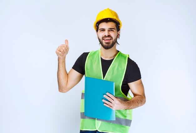 Dziewczyna w żółtym kasku trzymająca niebieską teczkę i pokazująca znak przyjemności.