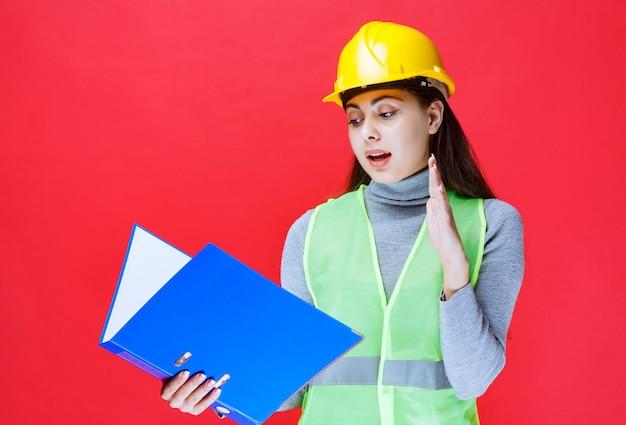 Dziewczyna w żółtym kasku z raportami podnosi rękę na uwagę.