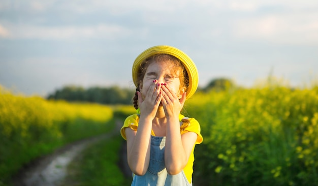 Dziewczyna w żółtym kwitnącym polu zakryła nos i twarz rękami i pomarszczyła się - nieprzyjemny zapach, podrażnienie, alergia. reakcja alergiczna na kwitnienie wiosną i latem, odstraszacz komarów