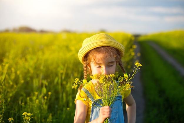 Dziewczyna w żółtym letnim polu wącha bukiet kwiatów. słoneczny dzień, święta, uczulenie na kwitnienie, wolność