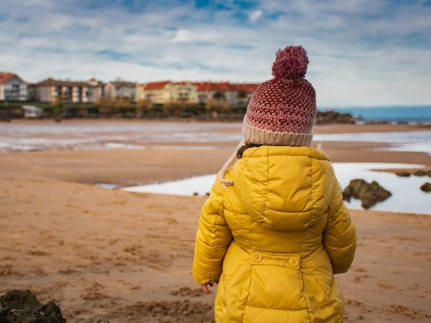 Dziewczyna w żółtym płaszczu i wełnianym kapeluszu, oglądając zimą plażę