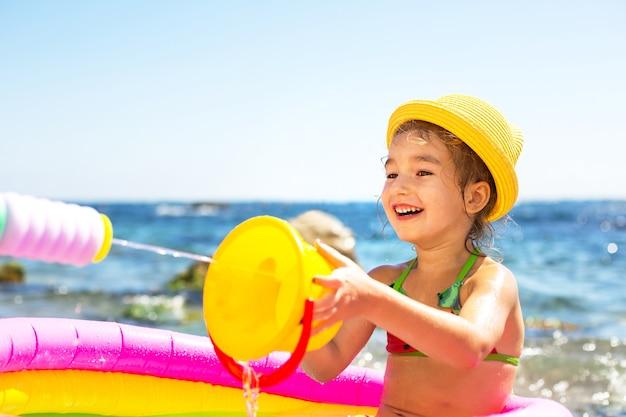 Dziewczyna w żółtym słomkowym kapeluszu bawi się dystrybutorem wody na plaży