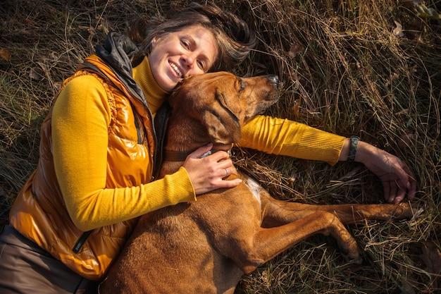 Dziewczyna w żółtym swetrze i rhodesian ridgeback leżą razem na jesiennej trawie