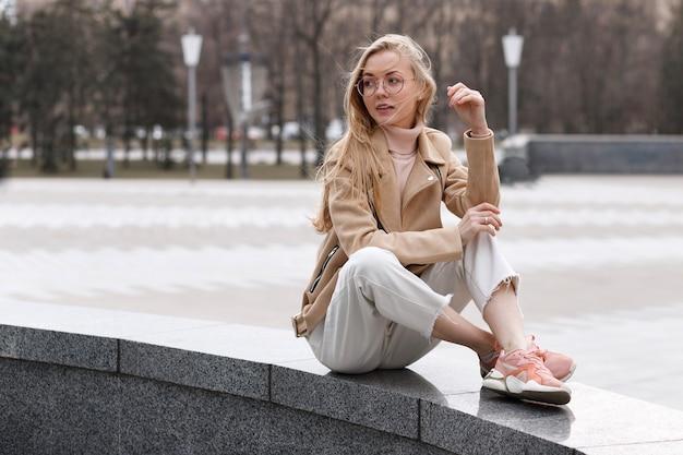 Dziewczyna w zwykłych ciuchach siedzi na mieście i patrzy w bok