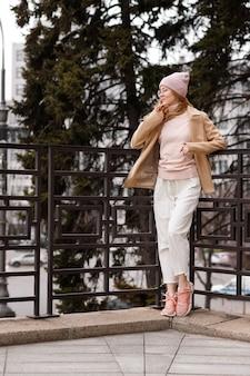 Dziewczyna w zwykłych ubraniach, okularach i benie pozuje na mieście i patrzy w bok