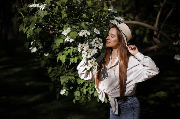 Dziewczyna wącha białych kwiaty w lato parku. zdrowa skóra.