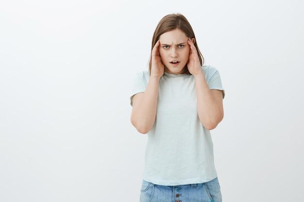 Dziewczyna wariuje od mnóstwa informacji, marszcząc brwi, trzymając ręce na skroniach, patrząc sfrustrowany, intensywnie próbując dowiedzieć się, jak rozwiązać kłopotliwą sytuację stojąc skupiona na białej ścianie