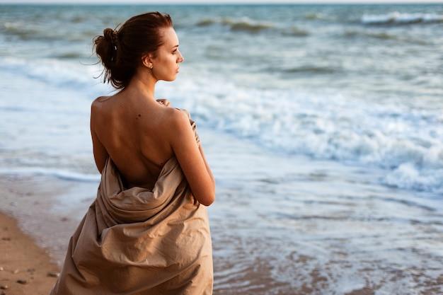 Dziewczyna wieczorem nad brzegiem morza stoi samotnie patrząc w dal na plaży o zachodzie słońca letni wieczór nad wodą piękna młoda kobieta owinięta kocem