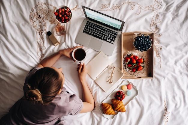 Dziewczyna wieczorem siedzi w łóżku ze smartfonem w dłoni i zjada truskawki, dziewczyna w łóżku je słodycze przed pójściem spać.