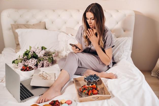 Dziewczyna wieczorem siedzi w łóżku ze smartfonem w dłoni i zjada truskawki, dziewczyna w łóżku przed pójściem spać je słodycze.