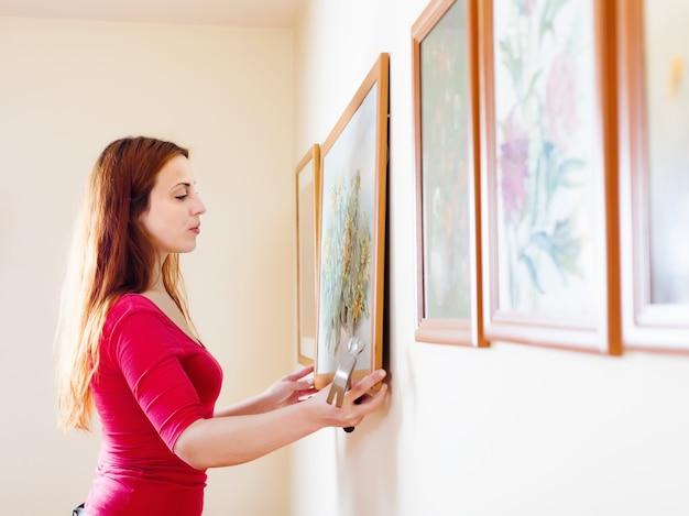 Dziewczyna wiszące zdjęcia w ramkach na ścianie