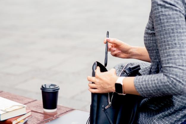 Dziewczyna wkłada długopis do czarnego plecaka