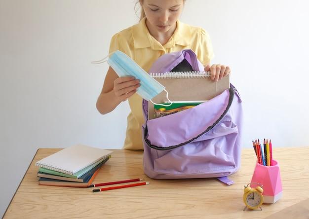 Dziewczyna wkłada do plecaka przybory szkolne i maskę ochronną