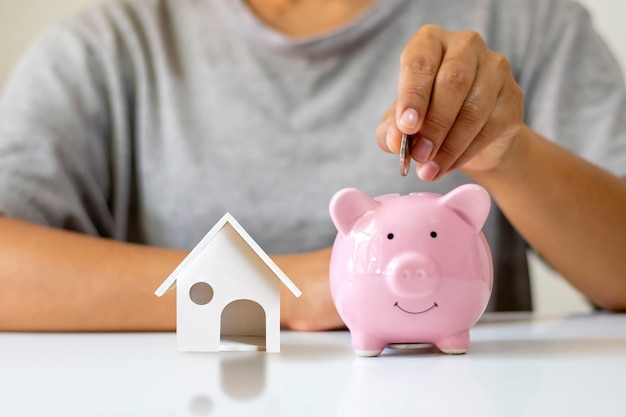 Dziewczyna wkłada pieniądze do świnki skarbonki i modelki domu