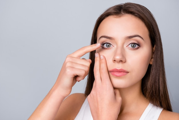 Dziewczyna wkłada soczewki kontaktowe do oczu