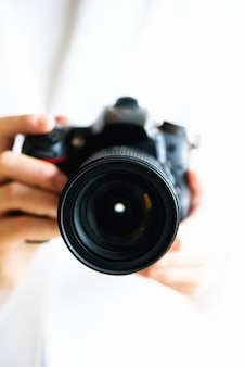 Dziewczyna wręcza mienie fotografii kamerę, biały tło, kopii przestrzeń. podróżuj i strzelaj