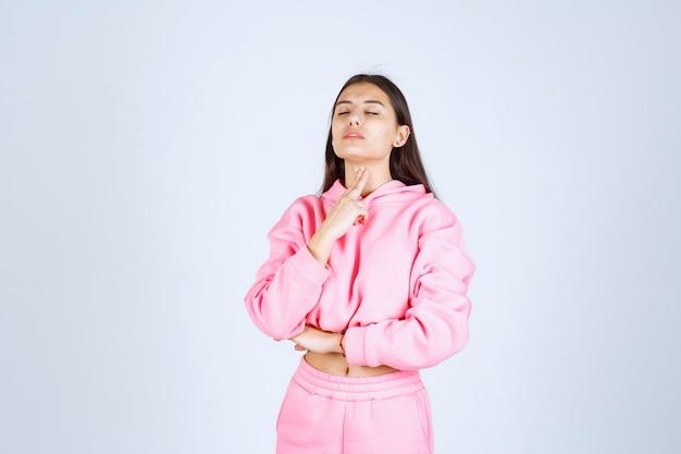 Dziewczyna wskazuje jej szyję, ponieważ ma ból gardła