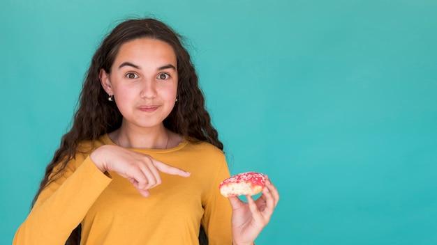 Dziewczyna wskazuje na szkliwionego pączka