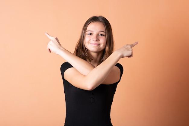 Dziewczyna wskazuje palcem w prawo, na jasnopomarańczowym tle. w dowolnym celu.