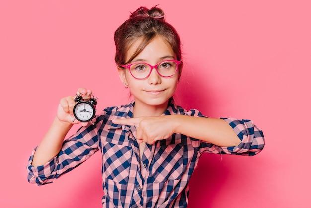 Dziewczyna wskazuje przy zegarem