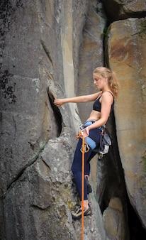 Dziewczyna wspinacz wspinaczka z liny i karabinki na stromej skalistej ścianie