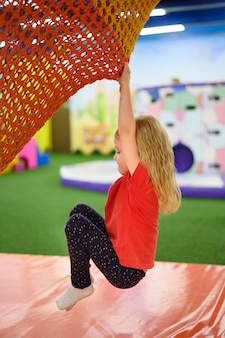 Dziewczyna, wspinaczka w widoku z boku placu zabaw