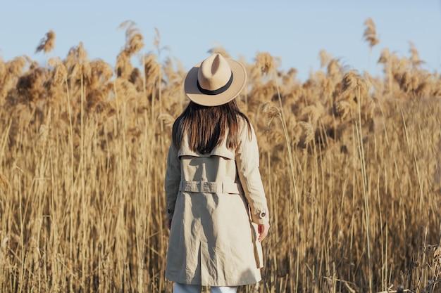 Dziewczyna wśród suchych puszystych trzcin w słoneczny dzień