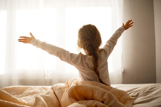 Dziewczyna wstała rano, siada na łóżku, wyciąga się i wygląda przez okno, dzień dobry i witaj słoneczko